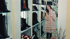 Beautiful brown-haired girl chooses a fur coat in the store. Shopping. Series - stock footage