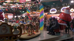 Parents sitting next to a Merry-go-Round at the Christmas market in Frankfurt Stock Footage