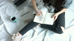 Overhead shot of Caucasian girl drawing letters in her notebook on bed Stock Footage