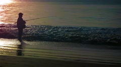 Local man fishing in the surf at dusk on a beach in Phuket, Thailand Stock Footage