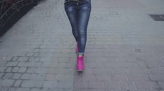 Fashionable woman in jeans and pink shoes is a street of the city Stock Footage