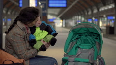Stock Video Footage of Mother put child into the stroller on station