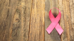Womens health symbol in pink ribbon on wooden board. Stock Footage