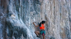 Female rock climber slowly climp up the rock with safety belt and ropes Stock Footage
