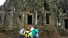 Tourists visiting Bayon Temple, an ancient Khmer religious site, Cambodia Stock Footage
