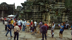 Tourists form long line to climb the steps into Angkor Temple, Cambodia Stock Footage