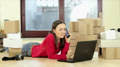 Young shopping woman at home with stack of boxes speaking by mobile HD Stock Footage