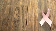Womens health symbol in a pink bow of ribbon on a wooden Board. Stock Footage