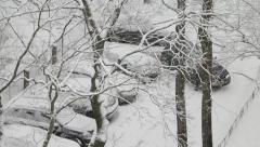 Car moving away from parking. Snow packt. High angle through tree branches. Stock Footage