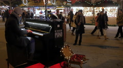 People looking at a man playing the piano at the Christmas market in Frankfurt - stock footage