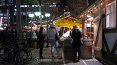 Women tasting food in front of the wine shop at the Christmas market, Frankfurt Stock Footage