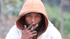 Portrait beggar man who smokes a cigarette. Mrauk U, Myanmar, Burma Stock Footage