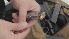 Man Loading Bullets Into a Pistol Magazine Stock Footage