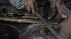 Close shot of filing of Sickle by an Indian blacksmith. Stock Footage