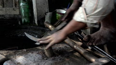 Mid close shot of filing of sickle by an Indian  blacksmith. - stock footage