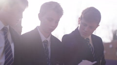 4K School boys looking at piece of paper outdoors in school playground Stock Footage
