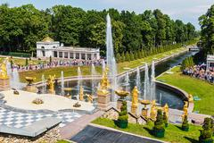 Tourists in Peterhof fountains of the Grand Cascade Stock Photos