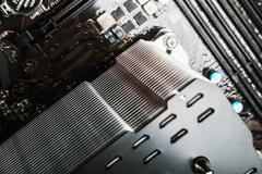 PC CPU cooler with heat pipes installed on mainboard - stock photo