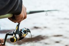 Hand holding a fishing rod with reel Stock Photos