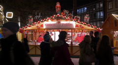 People passing by a candied fruits stall at the Christmas market in Frankfurt Stock Footage