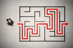 Lost businessman found the way in maze with red arrow - stock photo
