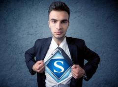 Businessman ripping off his shirt with superhero sign - stock photo