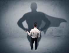 Successful businessman with superhero shadow Stock Photos