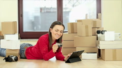 Smiling woman on line shopping using tablet and credit card in the room HD Stock Footage