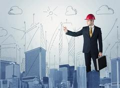 Stock Photo of Young worker drawing a city sight