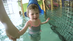 Toddler playing in kids pool at a recreational center. - stock footage