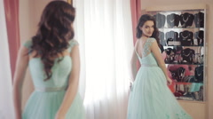Lovely woman admires into the mirror to choose a dress in a trendy salon Stock Footage