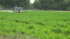 Village tractor spraying green maize corn crop field on rural farm. 4K Stock Footage