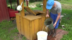 Male farmer guy draw water from well house and pour it to bucket. 4K Stock Footage