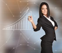 Office Girl draws bar graph standing on abstract background - stock photo