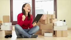 Excited shopping woman sitting with tablet and rejoicing her success HD - stock footage