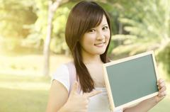 Asian college student pointing at blank chalkboard - stock photo