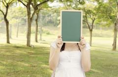 Asian female college student holding blank chalkboard - stock photo