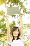 Asian college girl student with blank chalkboard - stock photo