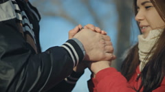 Boy warms hands girlfriend, frozen in the cold Stock Footage