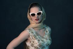 Stock Photo of Chique vintage 50s fashion woman wearing sunglasses and scarf around head.