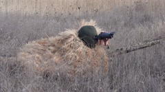 Stock Video Footage of Shooter Hunter looking through binoculars in ambush Slow Motion