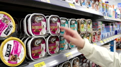 Woman buying Cesar dog food inside Walmart store Stock Footage