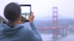 African American girl takes a photo of the Golden Gate bridge with her tablet Stock Footage