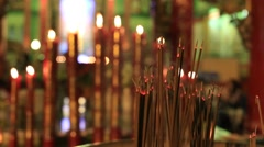 Incense sticks and wax candles burning in a Buddhist temple. Bangkok, Thailand Stock Footage