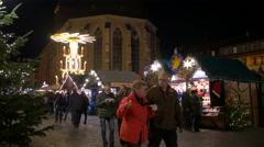 People walking near the Marktplatz's street stalls on Christmas in Heidelberg Stock Footage