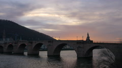 People walking on Alte Brucke at sunset in Heidelberg Stock Footage