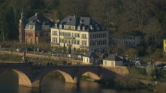People walking on Alte Brucke and cars driving on the street in Heidelberg Stock Footage