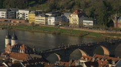People walking on the Old Bridge over Neckar River on a sunny day in Heidelberg Stock Footage