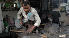 Mid shot of an Indian blacksmith filing a sickle. Stock Footage