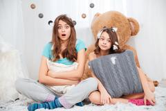 Two amazed lovely sisters sitting and hugging pillow Stock Photos